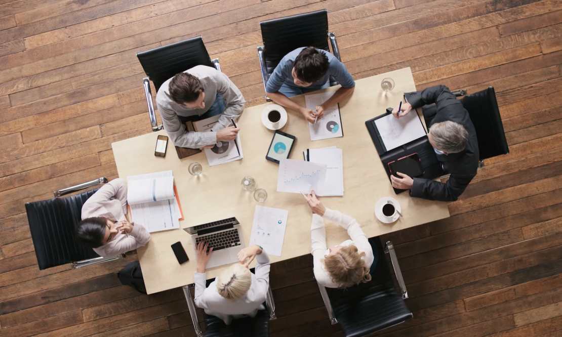 Aerial shot of 6 people meeting around a table