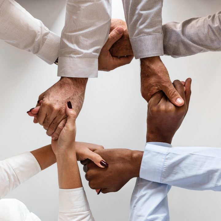 Four sets of hands join in the center